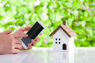 住宅とスマートフォンの操作,緑の背景