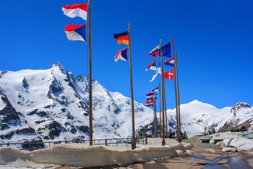 Flags hoover in the wind at the snow mountain background