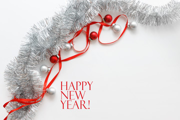 Greeting card template made of red ribbon, silver tinsel and balls with copy space, horizontal view, selective focus