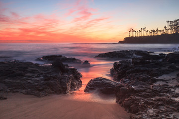 Long exposure of rocks and seaweed moss in waves, giving a mist like effect over ocean in Laguna Beach, California at sunset