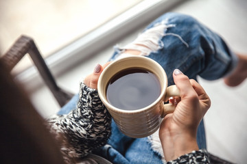 Girl's hands holding a cup of coffee, ripped jeans