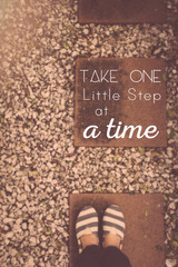 "Typography motivational quotation ""Take one little step at a time"", on blur background, vintage tone"