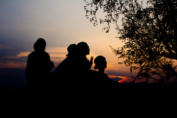 Silhouette of travelers enjoy their moment watching sunset