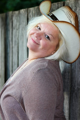 Grinning Woman Wearing Cowboy Hat Poses by Wooden Fence