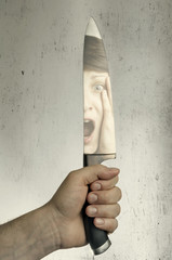 image of a hand with a large knife, a reflection of the face of the victim in the blade