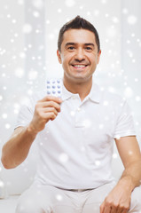 happy man showing pack of pills at home