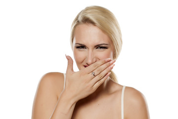 smiling woman covering her mouth with a hand