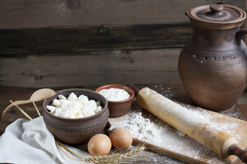 Rustic natural dairy products. Rustic natural dairy products cottage cheese, sour cream in clay dishes, eggs and ears of wheat on the old wooden background.