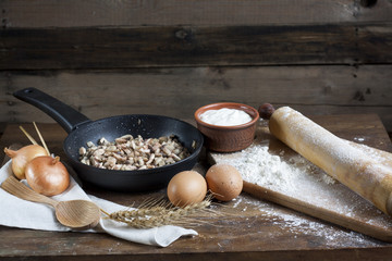 Rustic natural dairy products. Rustic natural dairy products sliced champignons mushrooms in a frying pan, sour cream in clay dishes, eggs, onions and ears of wheat on the old wooden background.