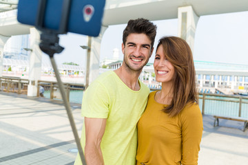 Caucasian couple take photo by cellphone stick