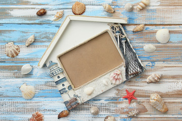 Summer sea decoration: lighthouse photo frame with star fish and shells on ocean color wooden background