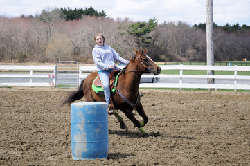 Pretty blonde teenage girl barrel racing; A young teenage girl turns around a barrel and races to the finish line