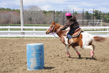 Teenage girl barrel racing; A young teenage girl turns around a barrel and races to the finish line
