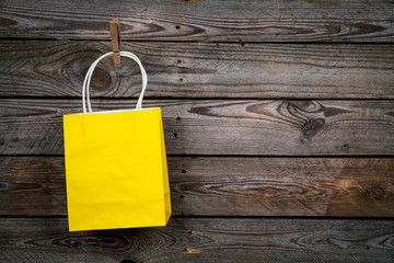 yellow Shopping bag on a wooden background, sale, purchase