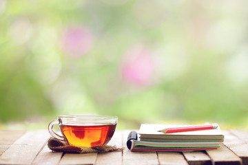 tea in glass and notebook with pencil at windows