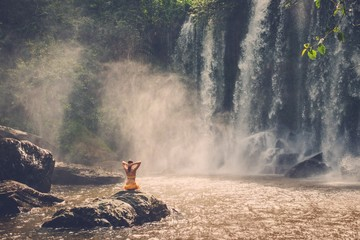 Beautiful woman sitting near waterfall enjoying the sun, Phnom Koulen at Siem Reap, Cambodia