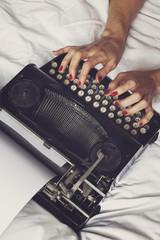femme en lingerie écrivant couchée avec machine à écrire vintage