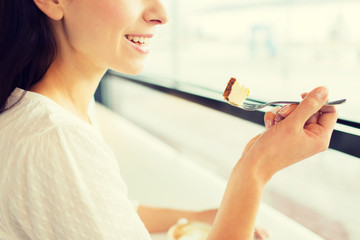 close up of woman eating cake at cafe or home