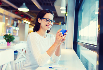 smiling woman with smartphone at cafe