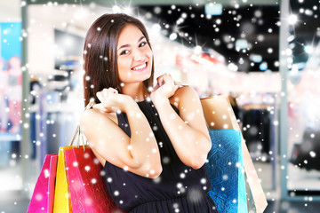 Beautiful young woman with shopping bags in the mall over snow effect