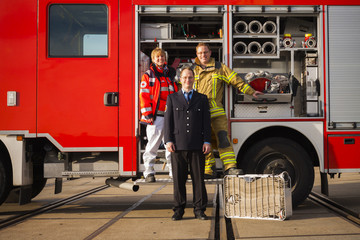Portrait of happy firefighters and paramedic woman standing together before fire engine truck