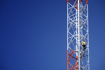 man painting on telecommunication tower.