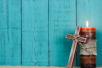 Candle and wooden cross by teal blue wood background