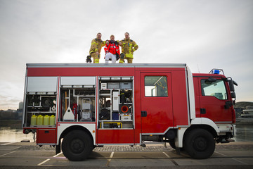 Firefighters and paramedic at the top of the fire engine truck