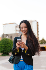Young woman using on smartphone while standing on street