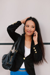 Elegant Asian Businesswoman in the Street Using a Mobile Phone