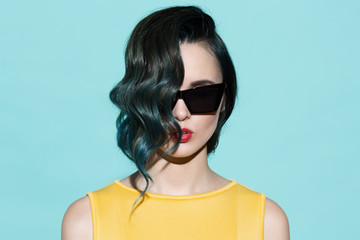 Fashion portrait of sensual stylish woman on a blue background.