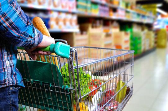 Man pushing shopping cart in the supermarket aisle