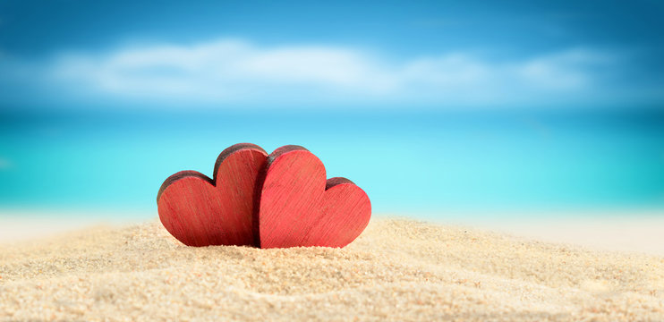 Two wooden hearts on the summer beach