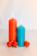 Two candles and three Christmas balls on a wooden surface