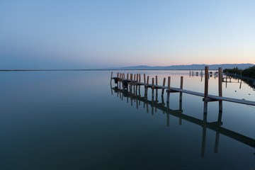 A calm sunrise by a wooden fishing pier.