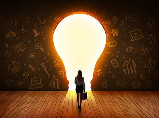 Business woman looking at bright light bulb in the wall