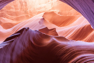 Magnificent nature sun filters into Lower Antelope Canyon Page Arizona USA while the shapes and swirls create and abstract nature image and silica in sandstone reflects some intense colors.