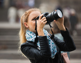 girl taking pictures of sights at city excursion