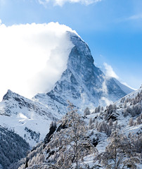 Amazing view on Matterhorn - famous mountain in Swiss Alps, with aerial view on Zermatt Valley, Switzerland, in a sunny winter day, with blue sky, clouds and view on ski resort