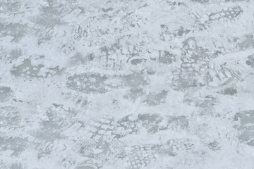 Icing. Texture, background.  Winter. The ice and snow is on the sidewalk after thawing . Traces of passersby has imprinted on the snow.