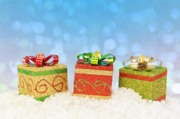 Present box ornaments on snow with abstract background