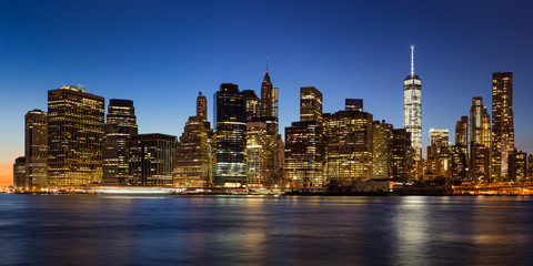 Fotomurales - New York City skyline of Lower Manhattan Financial District at twilight. Panoramic view has illuminated skyscraper rising above the East River.