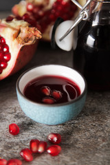 pomegranate juice in a blue circle and juicy red garnet. on a gr