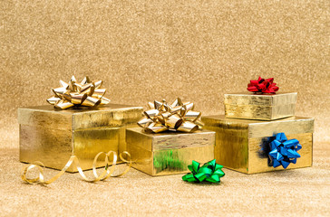 Gift boxes with ribbon bow over golden background