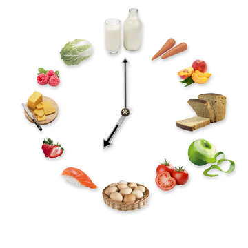 Clock arranged from healthy food products isolated on white back