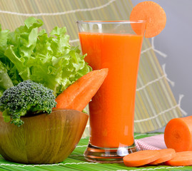 Fresh carrot juice with vegetables on wooden background