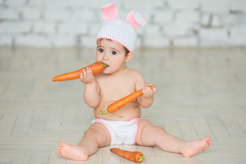 Portrait of a cute baby dressed in bunny ears sitting and eating  carrot