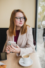 Young businesswoman looking throught a window at a coffe shop