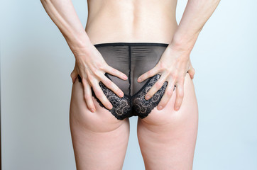 Woman in black lingerie clasping her bum