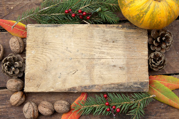 Pumpkin on wooden background - Halloween, Christmas and Thanksgiving concept border - frame - wallnut, pinecone, fir tree, berry and leaves decoration - copy space
